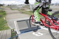 Community BMX Track. A child races a BMX bike on a community track Royalty Free Stock Photo