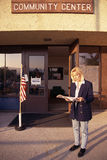 Community center. Woman reading in front of community center Royalty Free Stock Photography