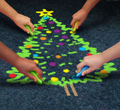 Community Christmas. Concept as a group of multicultural children drawing a decorated pine tree on the floor using chalk  as a winter holiday symbol for Stock Photo