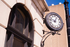 Community Clock Mounted on Building Close Corner Sidewalk Royalty Free Stock Photos