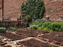Community Garden Plots. Neighborhood community garden plots of dirt framed in red bricks ready for planting Royalty Free Stock Photo