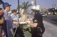 Community members giving lunch to policeman Royalty Free Stock Photo