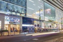 Communters fuera de tiendas de lujo de la marca en Hong Kong Foto de archivo libre de regalías