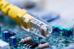 Commutateur jaune d'Internet sur la carte d'ordinateur, fibres optiques rougeoyantes étroites vers le haut du macro tir photographie stock libre de droits