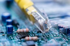 Commutateur jaune d'Internet sur la carte d'ordinateur, fibres optiques rougeoyantes étroites vers le haut du macro tir images stock