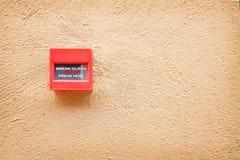 Commutateur rouge coloré d'alarme d'incendie sur le mur en béton brun, cassant le fond en verre de signe photo libre de droits
