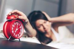Commutateurs de jeune femme le réveil sur le lit pendant le matin photographie stock