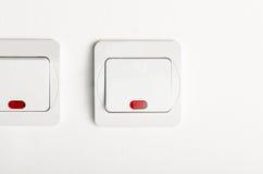 Commutatore di luce bianca inserita/disinserita sulla parete bianca con rosso principale Fotografia Stock