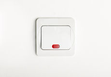 Commutatore di luce bianca inserita/disinserita sulla parete bianca con rosso principale Immagini Stock