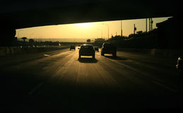 Commute. Highway traffic drives into the sun Stock Image
