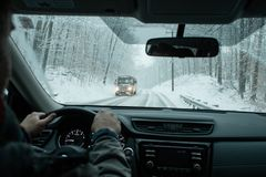 A commuter driving in a winter snow storm. A commuter driving on icy roads in a winter snow storm in New England stock photo