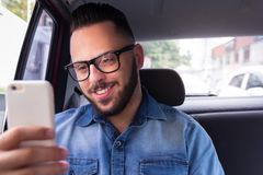 Commuter student man with glasses on smartphone using app texting message in back seat of car. Concept of commute, connection, as royalty free stock photo