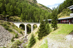 Commuter train is approaching a bridge in the picturesque Swiss Alpes. Royalty Free Stock Photography