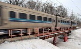 Commuter train crossing bridge. Winter scenery of commuter train crossing bridge at a high rate of speed Royalty Free Stock Photography