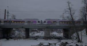 Commuter train crossing the bridge in Helsinki. Winter scene. HELSINKI, FINLAND - JANUARY 07, 2017: Modern commuter train moving over the bridge in snowy city stock video