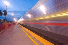 Commuter Train departing at Twilight. A sleek, illuminated commuter train rushing out of the San Carlos, CA train station at twilight.  San Carlos is located on Royalty Free Stock Images
