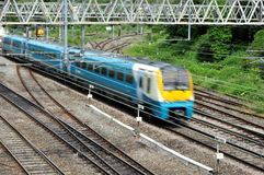 Commuter Train. English rail network with a blue commuter train rushing by stock photography
