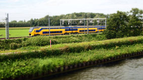 Commuter train moving through the countryside along farmland and Bank on the summer day Royalty Free Stock Photos