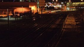 Commuter train at night. A commuter train going through the train yards at night stock footage