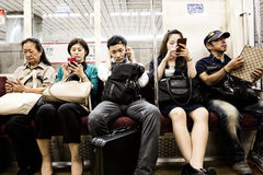 Commuter train passengers. TOKYO, JAPAN - 24 JUNE 2016 - Commuters with their mobile phones on a subway train in Tokyo, Japan. High contrast processing Royalty Free Stock Image