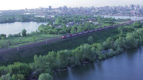 Commuter train passes by rail on city background stock footage