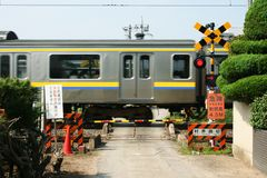 Commuter train passing by narrow crossing in Japan Stock Photos