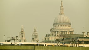 Commuter train passing by, St Paul's cathedral in the background. Train passing from Cannon Street station. In the background the St Paul's Cathedral, an iconic stock footage