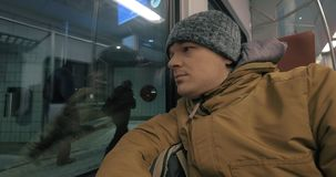 Commuter train ride in winter evening. Cinemagraph - Man commuter traveling by train in winter evening. He looking at the station, unidentified passengers stock footage