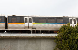 Commuter Train Speeding Past. A speeding rapid transit rail train passing over a raised platform Stock Photo
