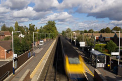 Commuter train speeding by station Royalty Free Stock Images