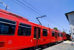 Commuter train at station. Bright red commuter train passing through a station or stop Stock Photo