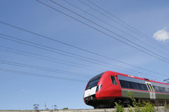 Commuter train zooming past. High-speed commuter-train on the move, surrounded by countryside and blue-sky Stock Photos
