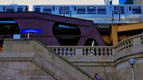 Man walks up stairs leading from Chicago Riverwalk to Wells Street as elevated `el` train passes on elevated track. royalty free stock image