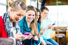 Commuters in cable car chatting on mobile phone Stock Photography