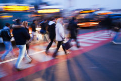 Commuters crossing the street. At a bus station in the evening Stock Image