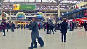 Commuters inside Victoria railway station in London. LONDON, UNITED KINGDOM Time table view timelapse panning of Commuters inside Victoria Railway Station stock video footage