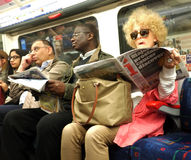 Commuters in London Underground. Commuters sit and some read papers during the rush our in London Underground,UK Royalty Free Stock Photos