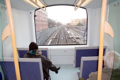 Commuters on metro train. Rear view of two commuters at back of urban metro train; tracks receding into distance out of window royalty free stock photo