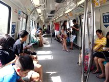 Commuters or passengers inside the MRT pass the time by playing games, watching videos, checking their email or updating their soc Stock Image