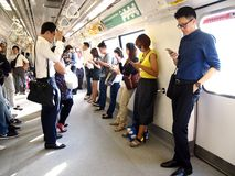 Commuters or passengers inside the MRT pass the time by playing games, watching videos, checking their email or updating their soc Stock Photos