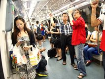 Commuters or passengers inside the MRT pass the time by playing games, watching videos, checking their email or updating their soc Stock Images