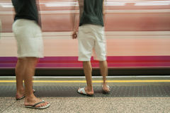 Commuters on platform. Commuters on platform, two men waiting for arriving train to stop Royalty Free Stock Photography