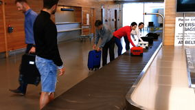Commuters taking their baggage from baggage carousel stock video
