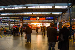 Commuters talk while waiting for their train to arrive. Late in the afternoon  at Munich Central Station Royalty Free Stock Photos