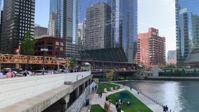 Commuters and tourists hurry along upper and lower city on Wacker Drive, riverwalk and water taxi. Commuters and tourists hurry along upper and lower city via stock video