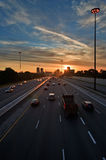 Commuters trying to beat the traffic at sunset. The beginning of morning rush hour, cars on the highway traveling to and from  downtown Stock Image