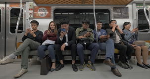 Commuters using mobile phones in subway. Seoul, South Korea