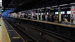 Commuters wait on a busy subway station platform at an underground station in Tokyo Japan. stock photography