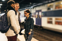 Commuters Waiting For Train. Young adults on their way to work, commuting on subway Royalty Free Stock Photos