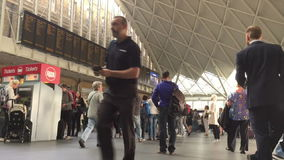 Commuters waiting for trains at Kings Cross station stock video